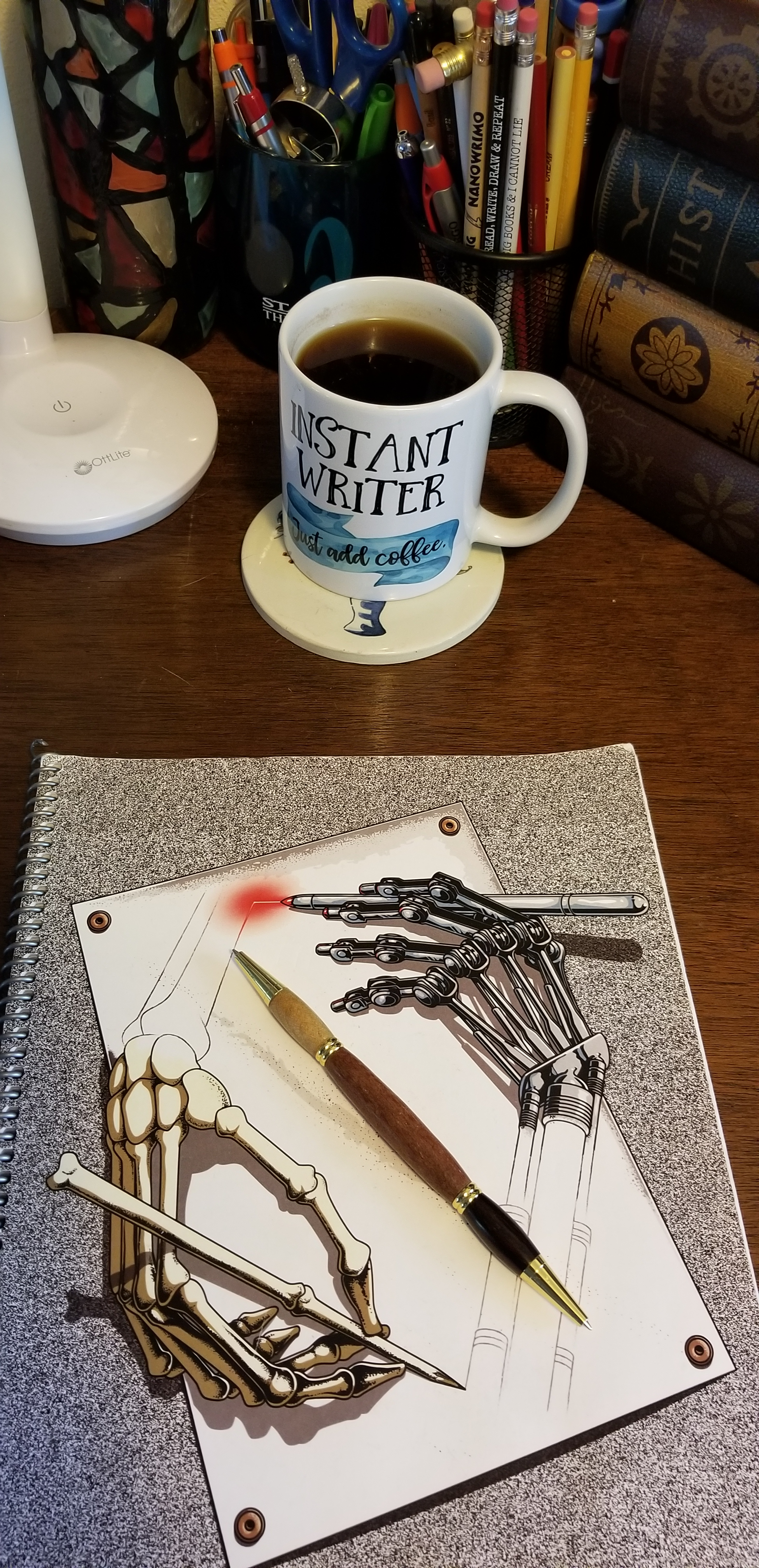 """Desk with a notepad and pen.  The notebook has two hands drawing each other.  One human hand with pencil. The other a metal hand with laser.  The pen is dual point and made with a wood barrel. A full coffee cup with the words """"Instant Writer,  just add coffee"""" is in the upper right corner of the desk.  Two cups are filled with pens and pencils.  The rest of the desk is covered with knickknacks."""